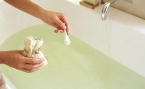 девушка добавляет в ванну соль
