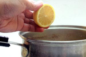 мужчина выжимает в кастрюлю лимон