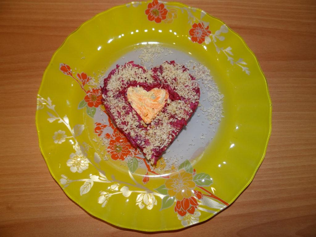 салат в виде сердечка на желтой тарелке